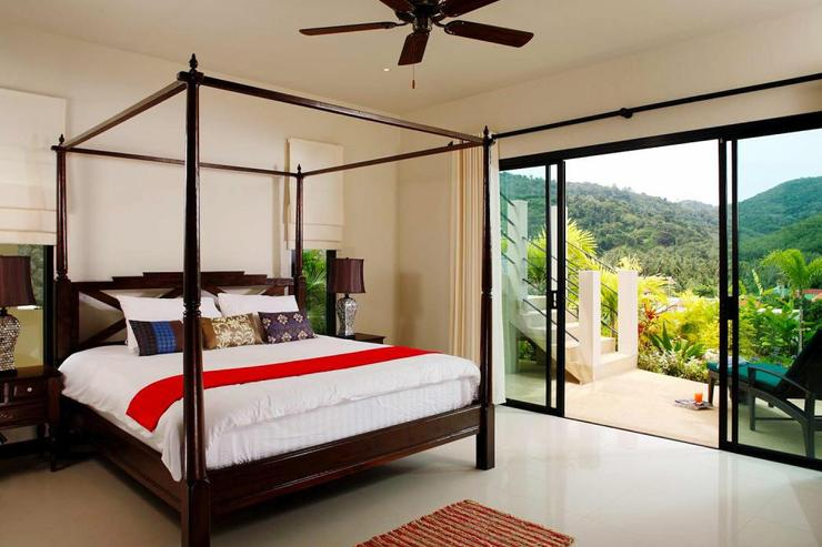 Bedroom 3 with four-poster king-size bed and sliding doors to sun deck and swimming pool