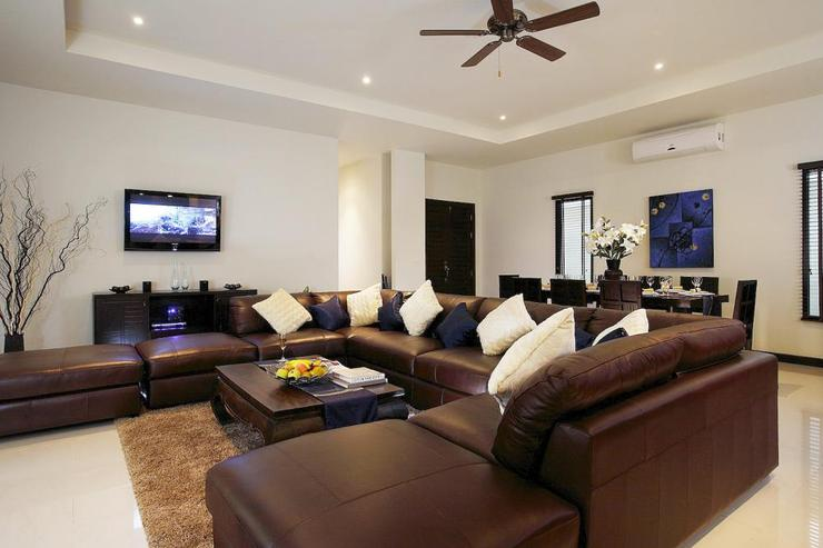 Spacious living room with huge leather sofa, with open plan dining room situatied behind