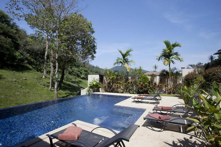 Swimming pool and surrounding sundeck, overlooking views across the valley