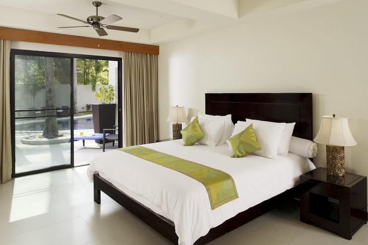Bedroom 4, located in self-contained area, with king-size bed, en-suite bathroom and sliding doors to sundeck and swimming pool