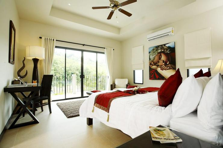 Master bedroom with king-size bed and sliding doors onto balcony