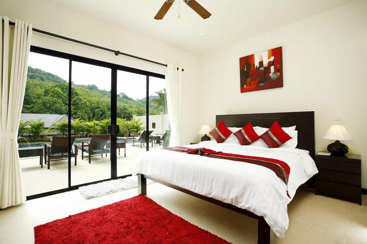 Bedroom 4 with king-size bed and sliding doors to outside sundeck and swimming pool