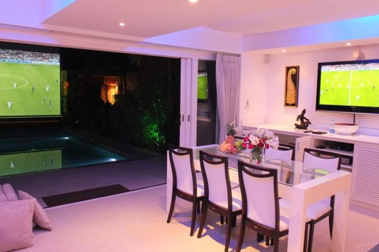 Villa Chok - Living area at night and projector screen near the pool