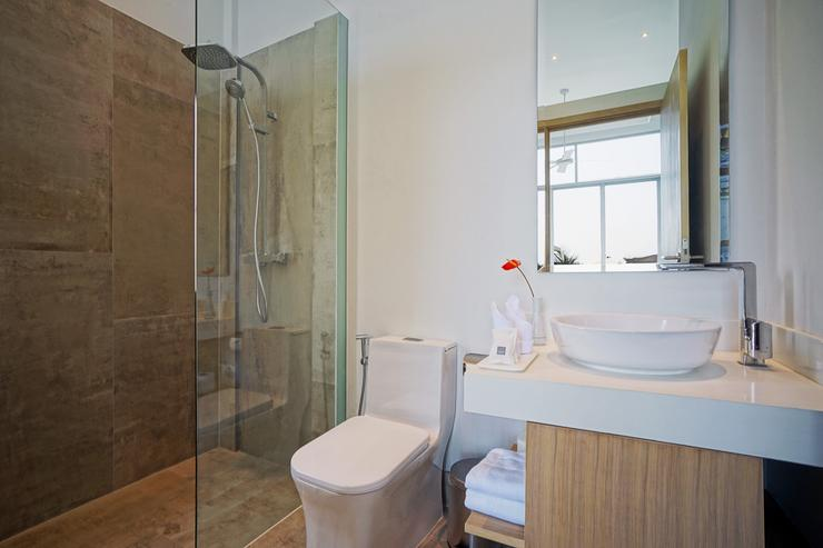 The Beach House - Bedroom 1's en-suite bathroom features contemporary fittings, luxurious marble tiles and shower enclosure with both rail and rain showers.
