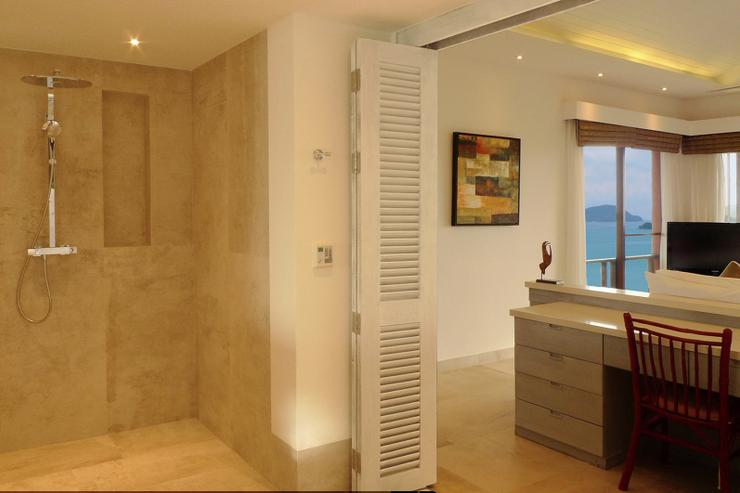 The large luxury bathroom of bedroom suite 2, finished in cooling floor-to-ceiling marble, is connected to the main bedroom by double folding doors