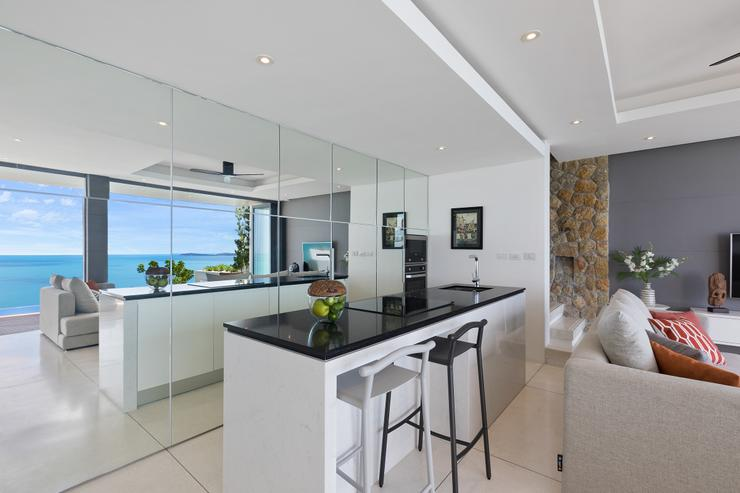 Villa Hanuman - A modern kitchen designed around a white marble island counter with its tall cabinets hidden behind mirrors